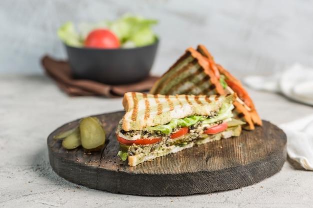 Sándwich de atún fresco, tomate, pepinillo y lechuga en pan tostado de cerca en el tablero de madera.