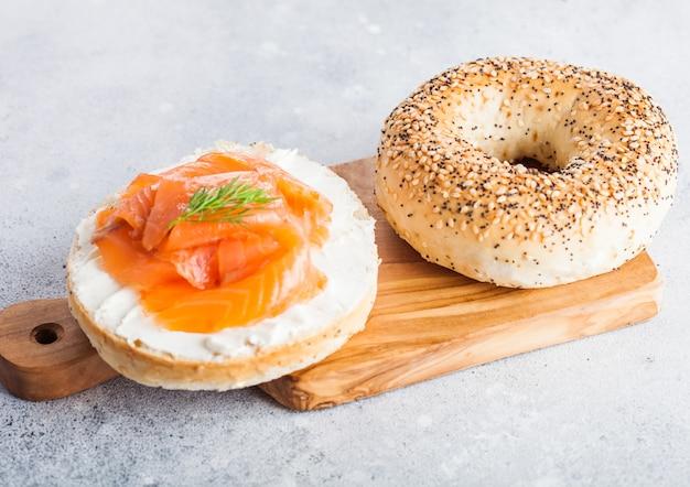 Sándwich de bagel saludable fresco con salmón, ricotta y eneldo en la tabla de cortar vintage en la mesa de la cocina ligera.