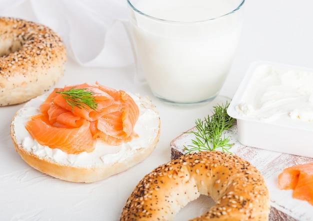 Sándwich de bagel saludable fresco con salmón, ricotta y vaso de leche en la mesa de la cocina ligera.