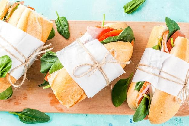 Sándwich de baguette fresco con tomate tocino queso y espinacas fondo azul claro