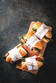 Sándwich de baguette fresco con tomate tocino queso y espinacas fondo azul oscuro