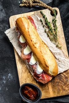 Sándwich de baguette con jamón serrano, paleta ibérica, queso camembert en la tabla de cortar.