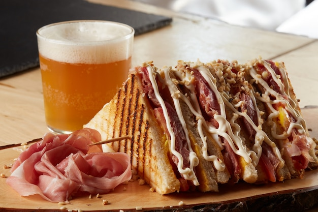 Sandwich en una bandeja de madera con una cerveza.