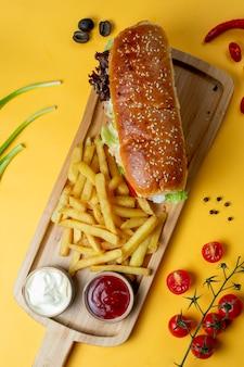 Sandwich con bollo de sésamo y papas fritas