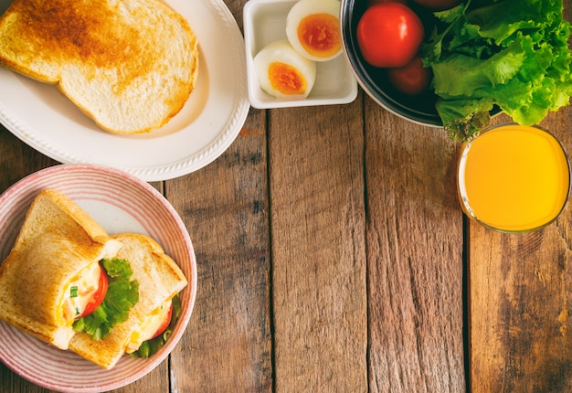 Sándwich de bolsillo y pan tostado con jugo de naranja para el desayuno en la mesa de madera con espacio de copia