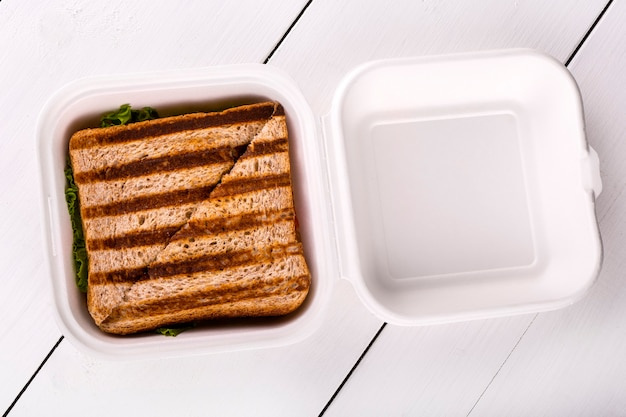 Sándwich caliente en un recipiente de plástico sobre mesa de madera blanca. vista desde arriba