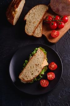Sandwich con carne de jamón de pavo, ensalada verde, queso y rodajas de tomates cherry frescos en un plato negro cerca de los ingredientes en la tabla de cortar, pared con textura oscura, vista superior