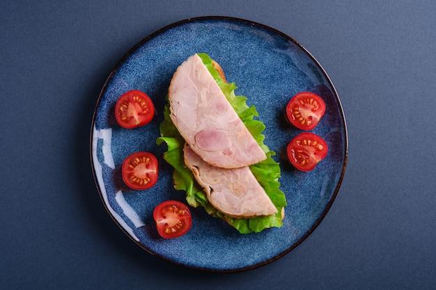 Sandwich con carne de jamón de pavo, ensalada verde y rodajas de tomates cherry frescos en placa azul brillante, pared mínima azul, vista superior