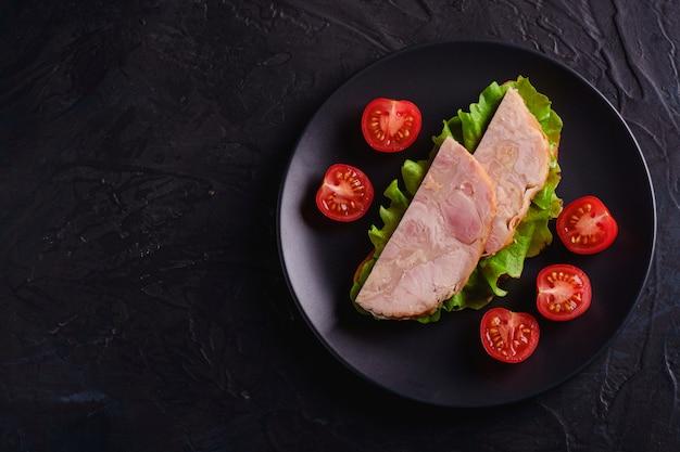 Sandwich con carne de jamón de pavo, ensalada verde y rodajas de tomates cherry frescos en placa negra, mesa con textura oscura, vista superior