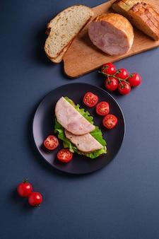 Sandwich con carne de jamón de pavo, ensalada verde y rodajas de tomates cherry frescos en un plato negro cerca de los ingredientes en la tabla de cortar, mesa mínima azul, vista superior