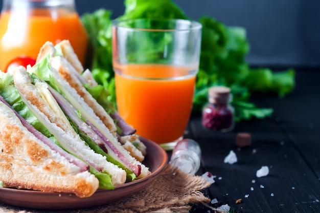 Sándwich casero con ensalada y jugo como desayuno saludable.