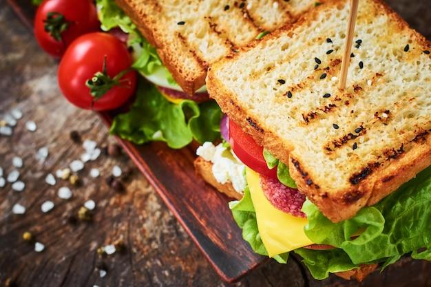 Sándwich casero con jamón, lechuga, queso y tomate sobre un fondo de madera