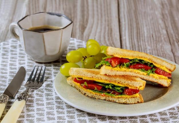 Sándwich casero de queso a la parrilla, uvas y café para el desayuno.