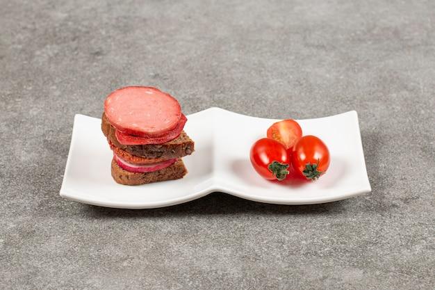 Sándwich casero y tomate en plato blanco.
