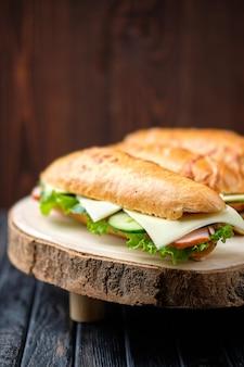 Sandwich de cazador con jamón, pepino, queso cheddar sobre tabla de madera (foto con poca profundidad de campo)