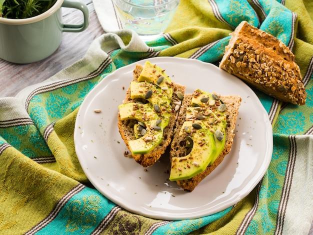 Sándwich de cereal de aguacate para una merienda saludable con semillas en una servilleta verde