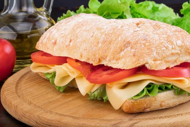 Sandwich de chapata con lechuga, jamón y queso sobre tabla de madera