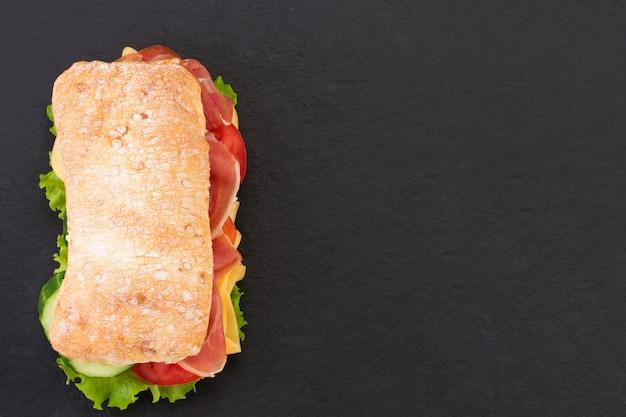 Sándwich de chapata con lechuga, jamón serrano y queso sobre piedra.