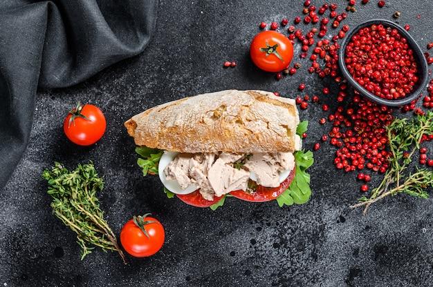 Sandwich de chapata con paté de hígado, rúcula, tomate, huevo y hierbas.