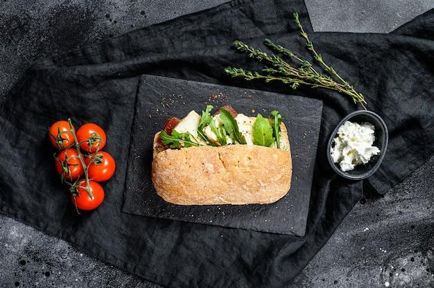 Sándwich de chapata con queso de cabra fresco, mermelada de pera y rúcula. superficie negra. vista superior