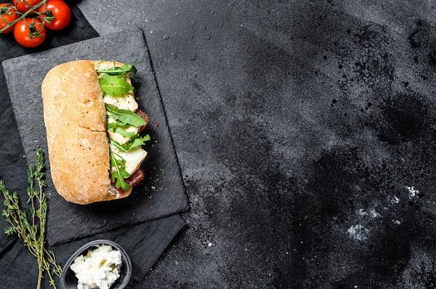 Sándwich de chapata con queso de cabra fresco, mermelada de pera y rúcula. vista superior.