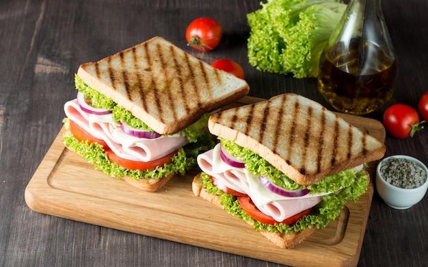 Un sándwich club con carne, ensalada, verduras.