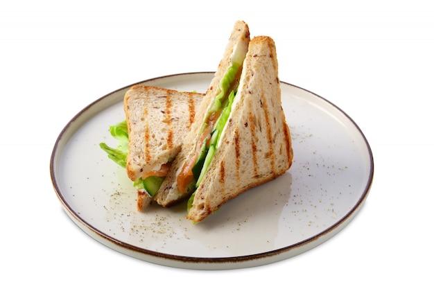 Sándwich club con salmón, pepino, ensalada y queso aislados en blanco