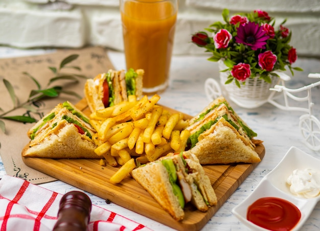 Sándwich club servido con papas fritas y refrescos, mayonesa, salsa de tomate