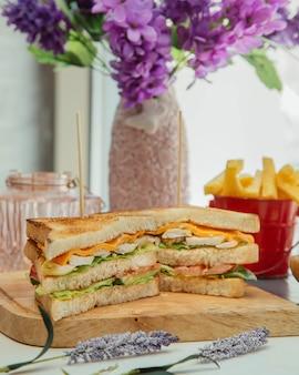 Sándwich club servido con papas fritas