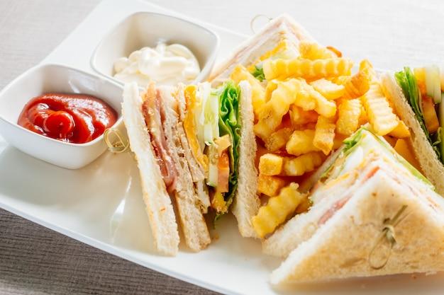 Sándwich club con verduras y salsa.