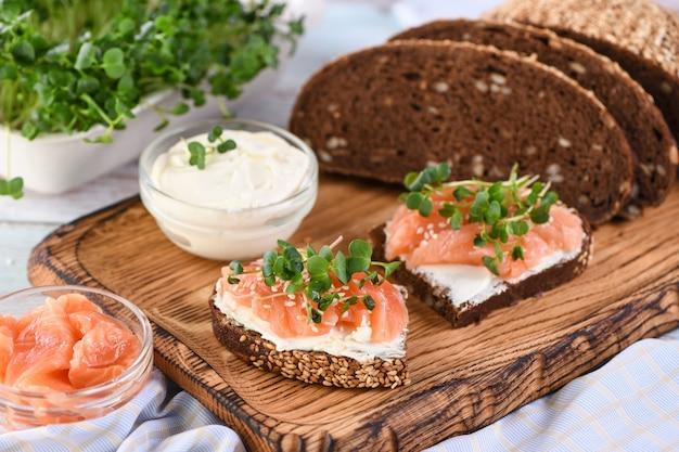 Sándwich con crema de queso sobre una rebanada de pan de centeno con cereales rebanadas de salmón marinado