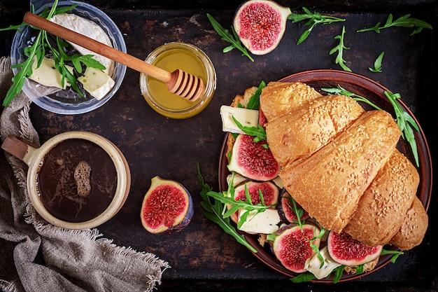 Sándwich de croissant fresco con rúcula de queso brie e higos. desayuno delicioso. comida sabrosa. endecha plana.