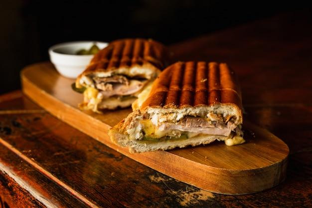 Sandwich cubano tradicional con queso, jamón y carne de cerdo frita, servido sobre una tabla de madera