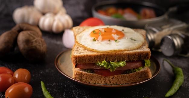 Sándwich de desayuno elaborado con pan, huevo frito, jamón y lechuga.