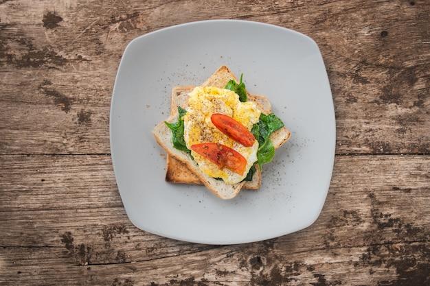 Sándwich de desayuno con huevo, berros y tomate en la mesa de madera, alimentos saludables