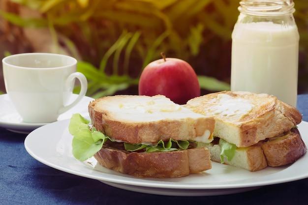 Sandwich desayuno con leche y café caliente por la mañana