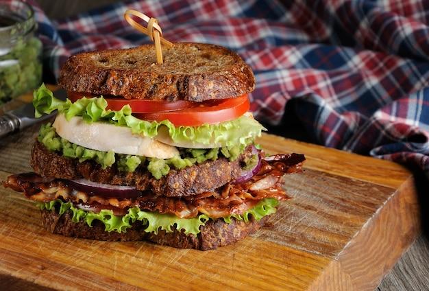 Un sándwich doble de pan griego con rebanadas de pechuga de pollo hervida con aguacate y tocino frito