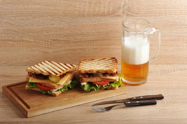Sandwich de dos capas con tocino y pechuga de pollo sobre una tabla de madera