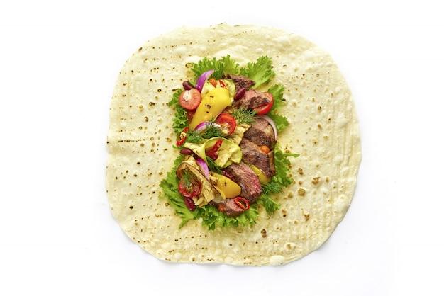 Sándwich de envoltura de tortilla abierta con jugoso bistec, verduras asadas, tomates cherry, ensalada de lechuga y hierbas, vista superior