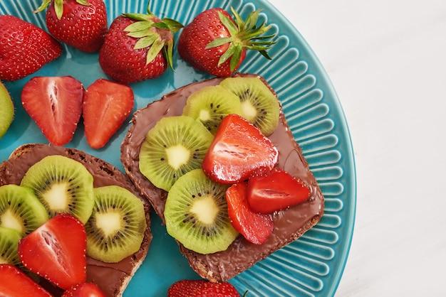 Sandwich de frutas, fresas y kiwi. tostadas de mantequilla de maní.