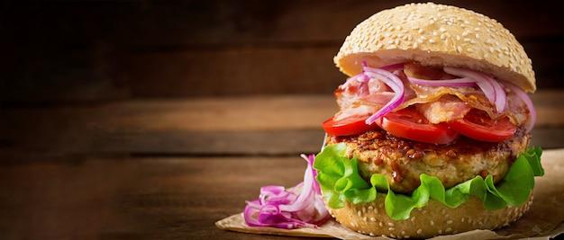 Sándwich grande - hamburguesa con carne de res, cebolla roja, tomate y tocino frito.