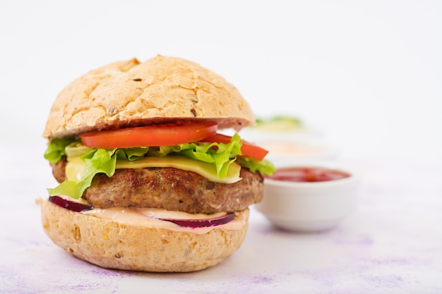 Sándwich grande: hamburguesa con jugosa hamburguesa de ternera, queso, tomate y cebolla roja en una mesa ligera y papas fritas.