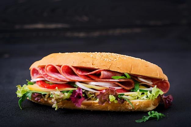 Sándwich grande con jamón, salami, tomate, pepino y hierbas.