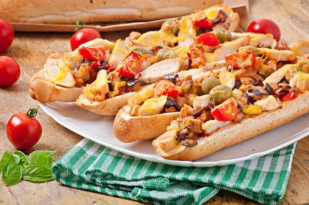 Sándwich grande con verduras asadas (calabacín, berenjenas, tomates) y pollo con queso y albahaca sobre fondo de madera vieja
