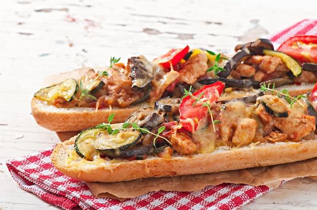 Sándwich grande con verduras asadas (calabacín, berenjenas, tomates) con queso y tomillo.