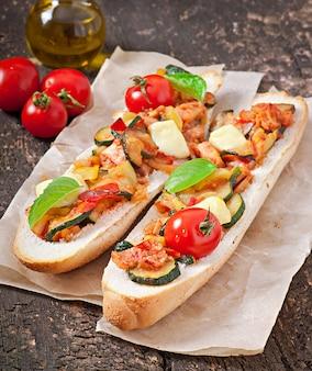 Sándwich grande con verduras asadas (calabacín, pimentón, tomate) con queso y albahaca sobre fondo de madera vieja