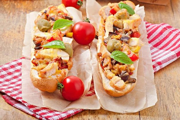 Sándwich grande con verduras asadas y pollo con queso y albahaca sobre superficie de madera vieja