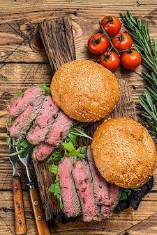 Sándwich de hamburguesa con cortes de carne de res, rúcula y espinacas