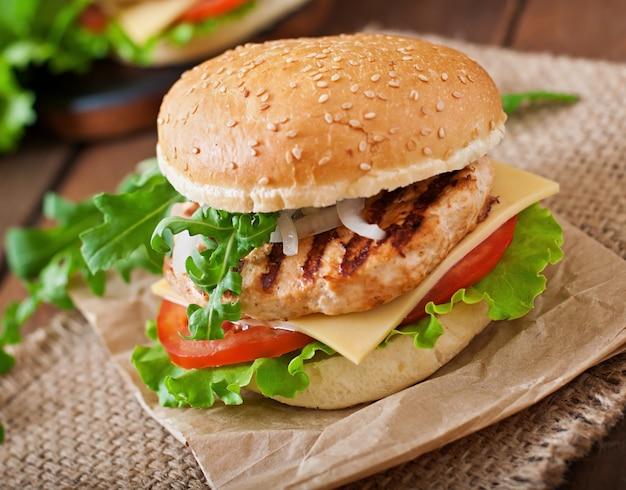 Sandwich con hamburguesa de pollo, tomate, queso y lechuga.
