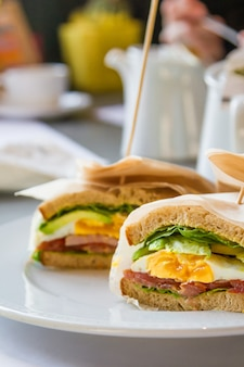Sándwich con huevo, jamón, aguacate en restaurante.